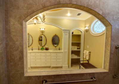 Looking out of the shower thru window in the shower at the linen closet and end of the vanity